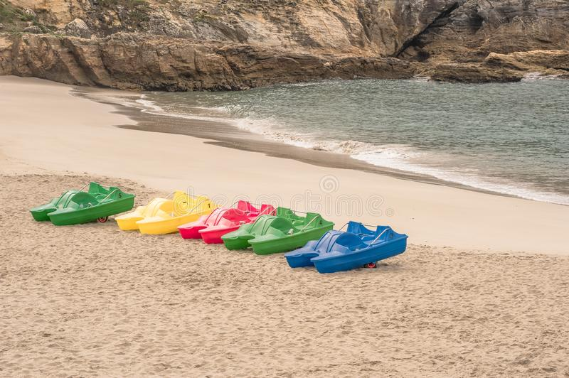 Colored pedal boats on sand beach royalty free stock image