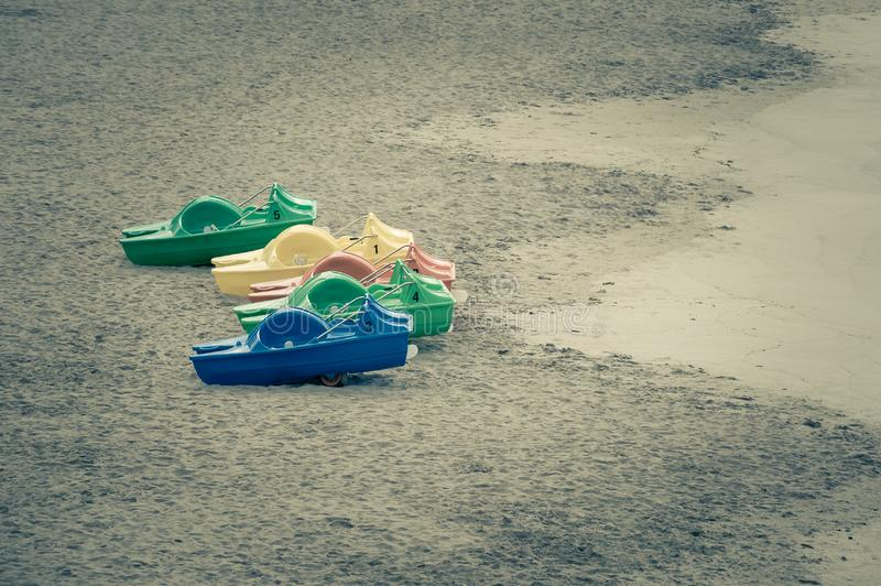 Colored pedal boats on sand beach stock photography