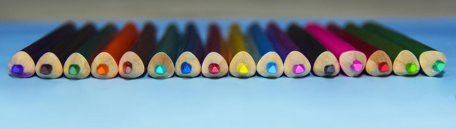 Colored pencils on a blue background close-up. Beautiful colored pencils royalty free stock photography