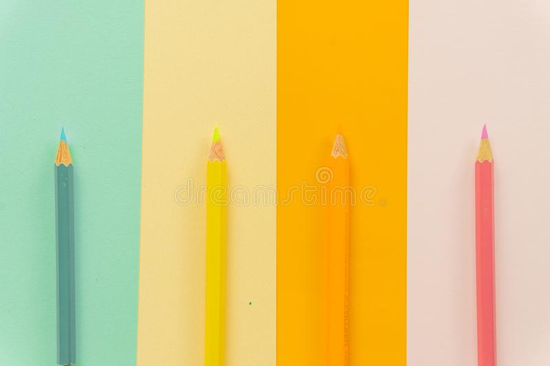 Colored pencils Blue, yellow, orange and pink on Blue, yellow, orange and pink background. stock image