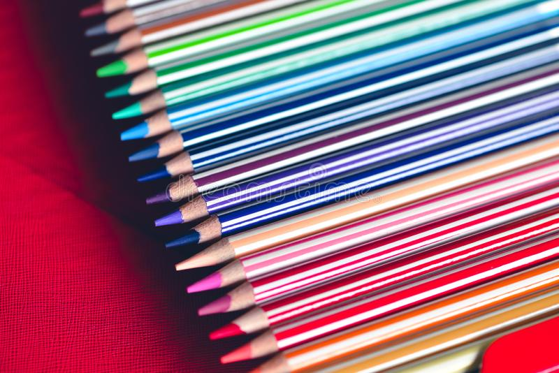 Colored pencils box closely. Watercolor wooden pencils set in colored stripes. For drawing, painting, creativity. Macro art tools photo on red background royalty free stock photography