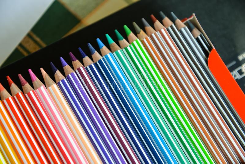 Colored pencils box closely. Watercolor wooden pencils set in colored stripes for drawing, painting, creativity. Macro art tools photo on blurred background stock photos