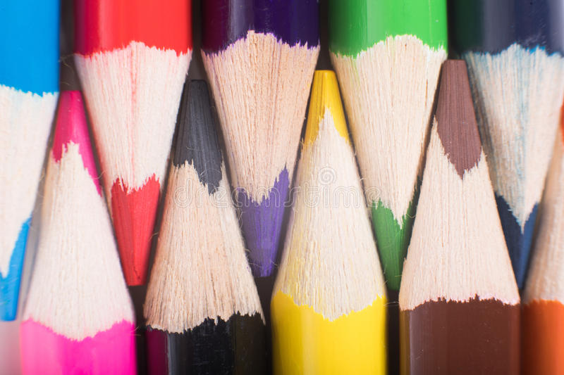 Colored pencils close-up. Colored pencils background concept in close-up full frame view, with sharpened tips in opposite to each other stock image
