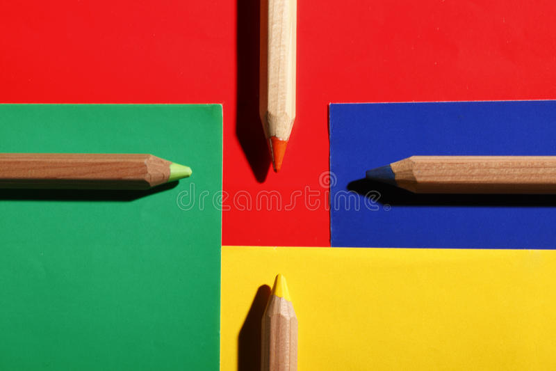 Colored pencils on colored papers arranged as a crossroads royalty free stock photography