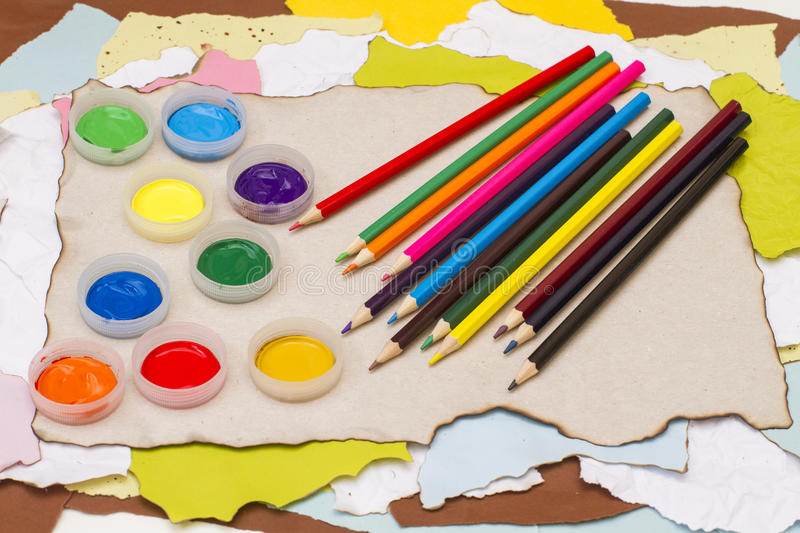 Colored pencils and cover with paint gouache royalty free stock image