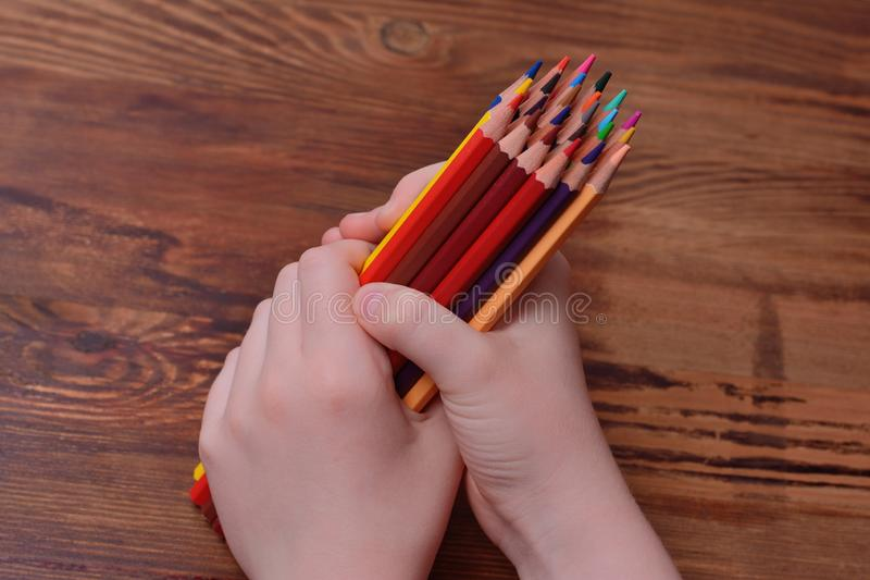Colored pencils in hands on a wooden background royalty free stock photos