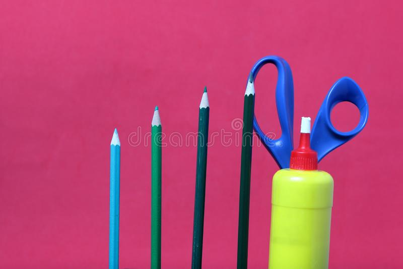 Colored pencils. They are located vertically. Scissors and glue for application. School supplies. Color pencils in green shades. Scissors and glue for royalty free stock images