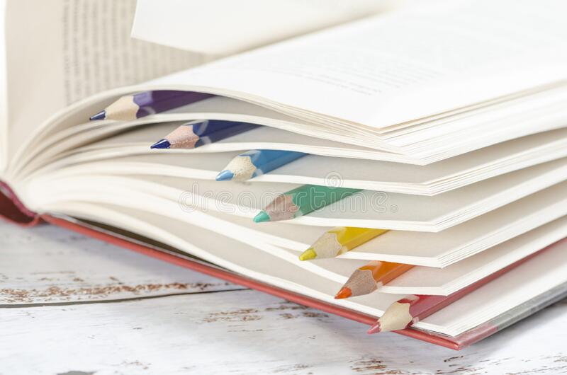 Colored pencils between pages of a book royalty free stock photos