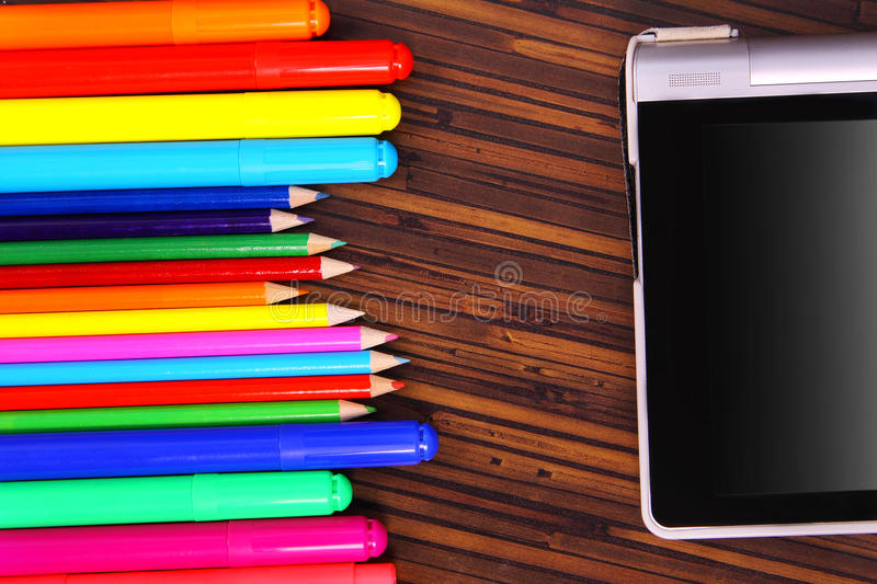 Colored pencils, and the plate on a wooden background stock images