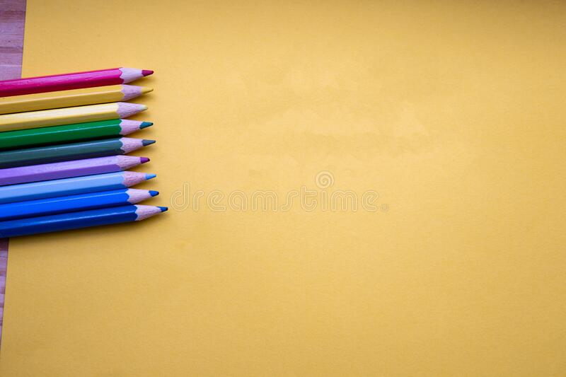 Colored pencils in Rainbow colors in a row on orange background, retro modern design space for text top view stock image