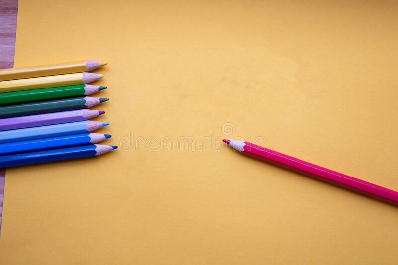 Colored pencils in Rainbow colors in a row on orange background, retro modern design space for text top view stock images