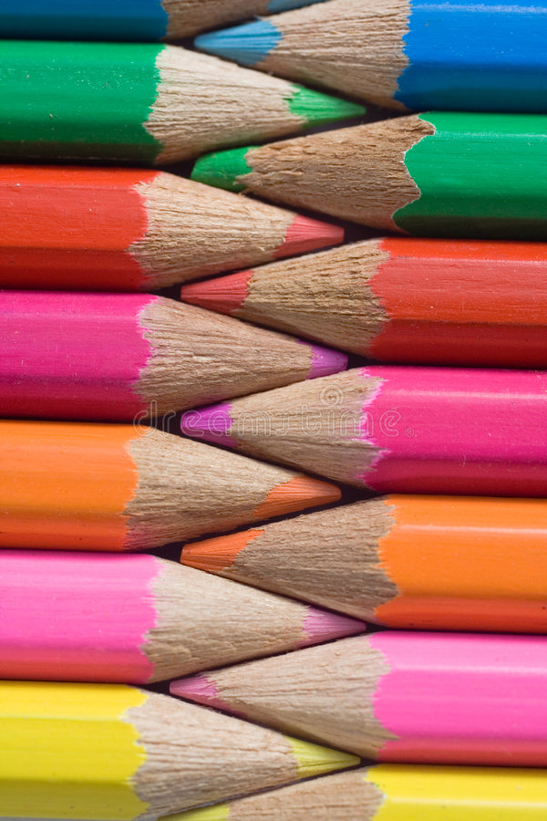 Colored Pencils In A Row. Colorfully arrangement of sharpened colored pencils stock photo
