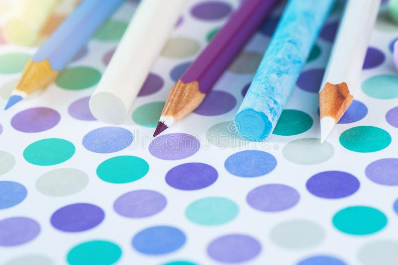 Colored pencils and school chalk on a pastel background to a point with space for text royalty free stock photography