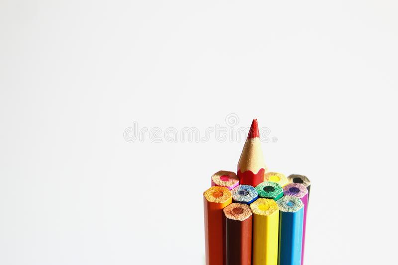 Colored pencils. Set of colored pencils with a single sharp one symbolizing leadership concept stock images