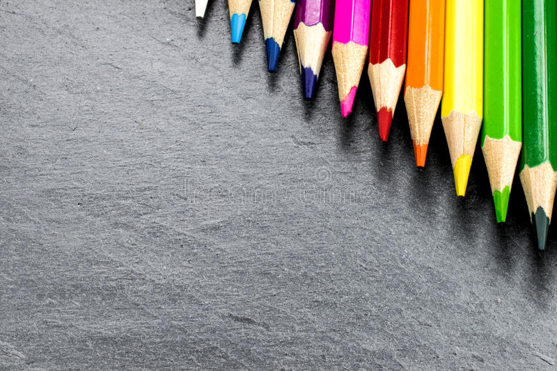 Colored pencils on slate royalty free stock images