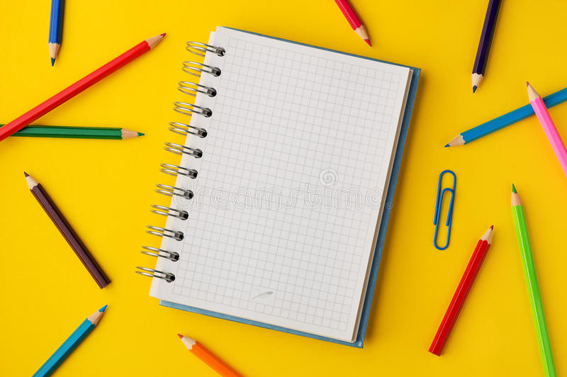 Colored pencils and squared paper note on yellow background stock photo