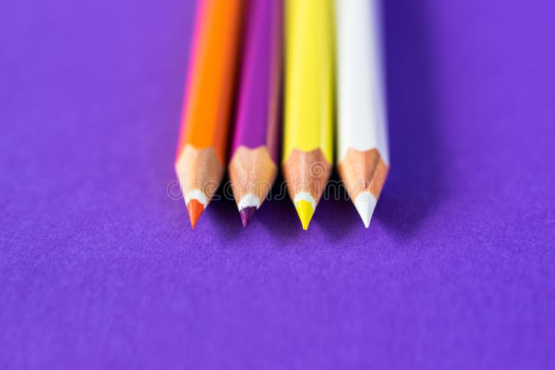Colored pencils on a violet background with space for text royalty free stock image