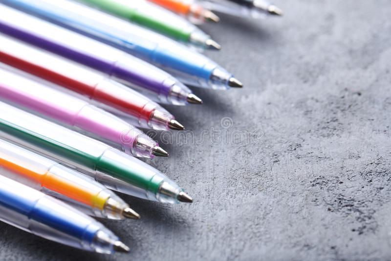 Colored pens. On a grey wooden table stock images