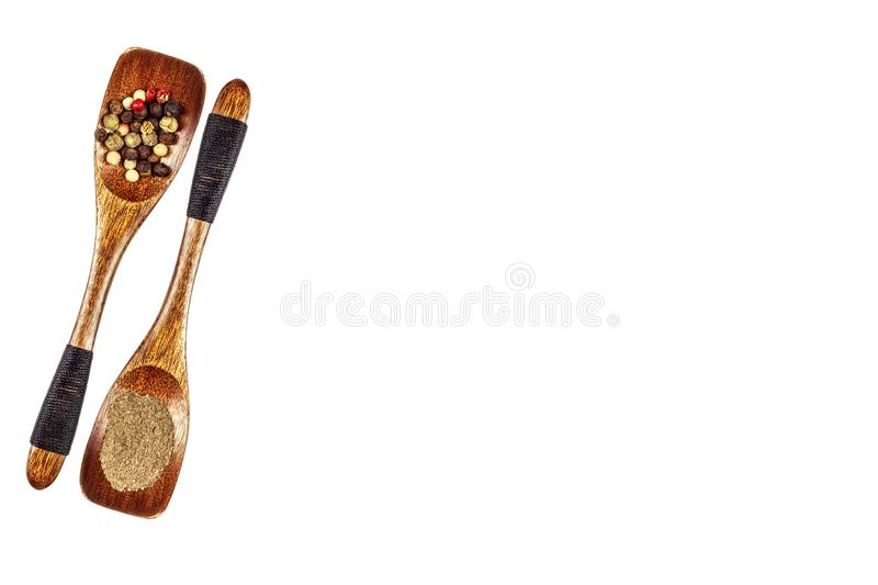 Colored pepper and ground pepper on a wooden spoon, isolated on white. Traditional aromatic spices. Medicinal spices. Colored pepper and ground pepper on a stock photos