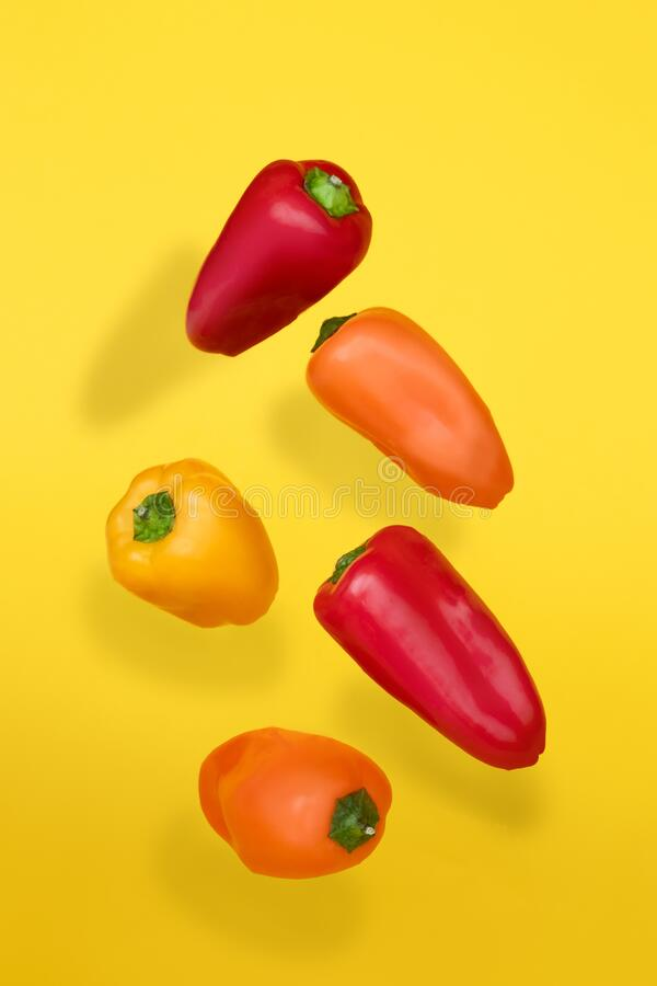 Colored peppers on a yellow background. Cooking concept royalty free stock photography