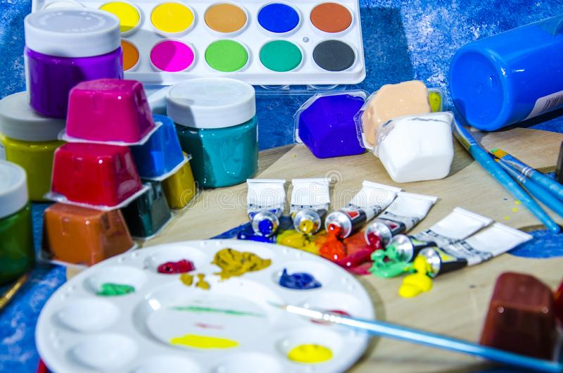 Color pigments. Colored pigments are packed in glass bottles, boxes and cans, oil brushes, palettes, oil paints, gouache pigments royalty free illustration