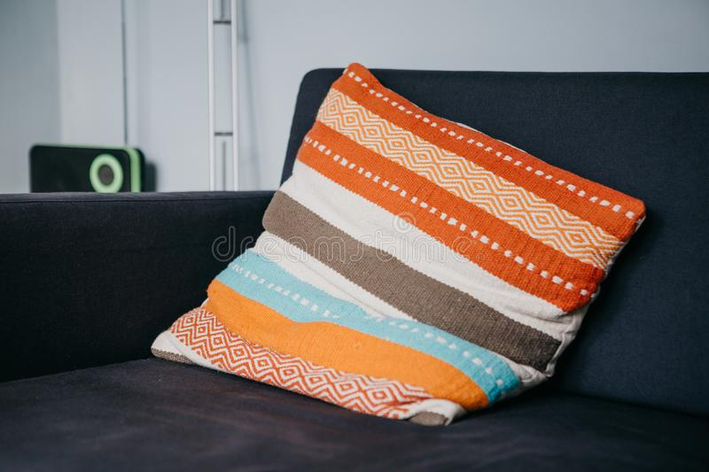 A colored pillow on the sofa in the living room. Cozy atmosphere royalty free stock photography