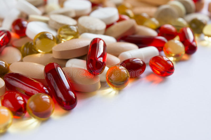 Colored pills on a white surface royalty free stock photography