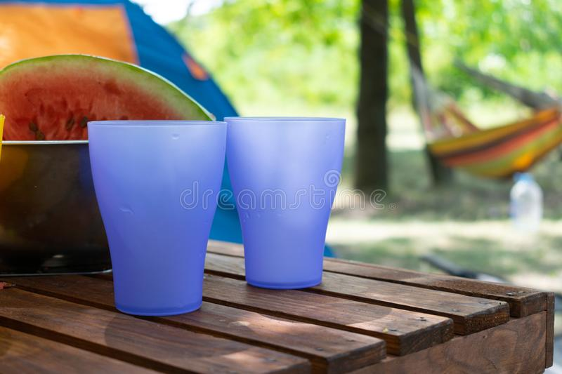 Colored plastic purple glasses, picnic utensils against tent and hammock background in Summer day.  picnic basket with plastic royalty free stock image