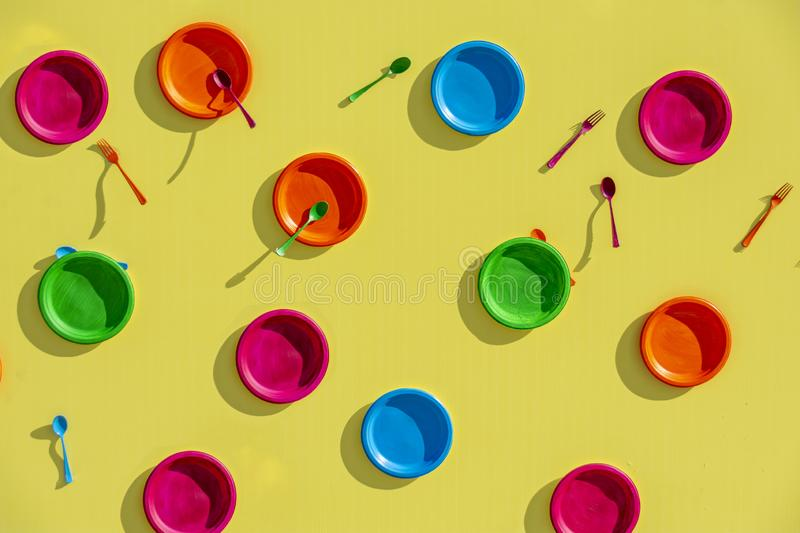 Colored plates on a fashionable yellow background. Conceptual, abstract background. Background food image for the holiday and royalty free stock image
