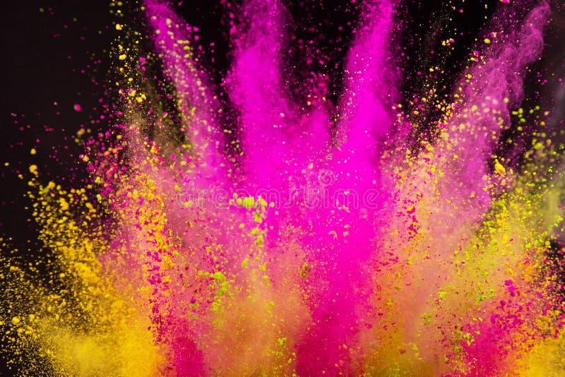 Colored powder explosion on black background. Freeze motion royalty free stock image