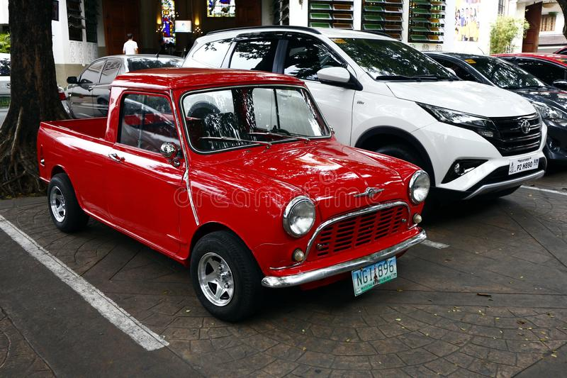 A colored red classic and vintage mini car. ANTIPOLO CITY, PHILIPPINES – JULY 12, 2019: A colored red classic and vintage mini car parked beside a modern stock photos