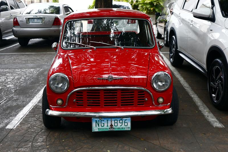 A colored red classic and vintage mini car. ANTIPOLO CITY, PHILIPPINES – JULY 12, 2019: A colored red classic and vintage mini car parked beside a modern royalty free stock photo
