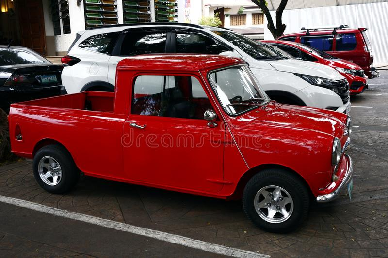 A colored red classic and vintage mini car. ANTIPOLO CITY, PHILIPPINES – JULY 12, 2019: A colored red classic and vintage mini car parked beside a modern royalty free stock photography