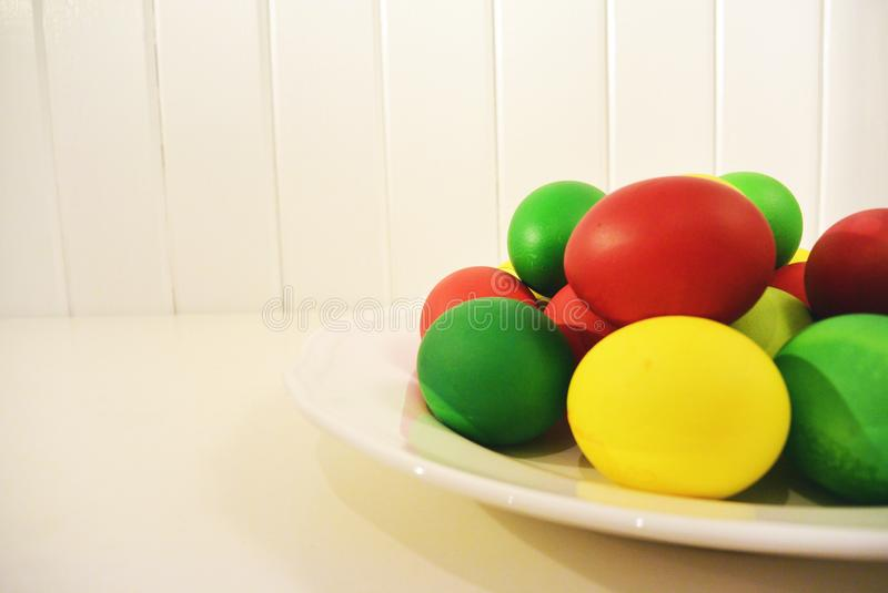Colored red green and yellow easter eggs on plate. royalty free stock photos