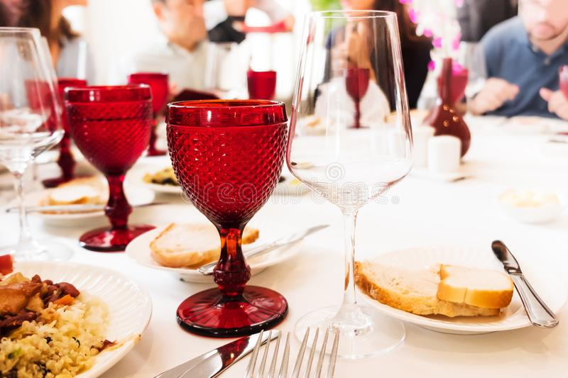 Colored red matte glasses and empty wineglasses on the table. Blurred people on background. royalty free stock photos
