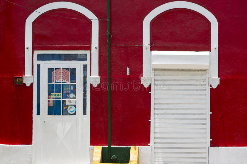 Colored red wall and white doors, colonial architecture in Venezuela. Red typical colonial architecture with white doors in Porlamar, Venezuela 2015 stock image
