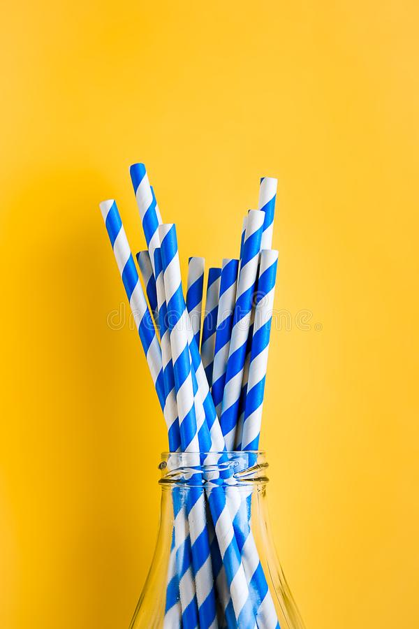 Colored, reusable, paper, striped, blue and white straws for drinking juice or cocktail life, in a glass bottle, on a yellow stock photos