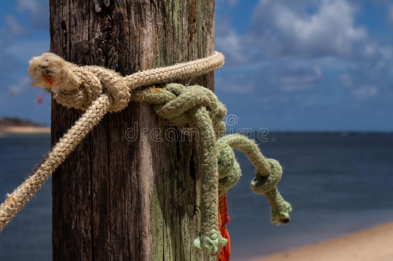 Colored ropes knotted on a pole. Knots at the edge of the sea. Tying and knotting concept royalty free stock image