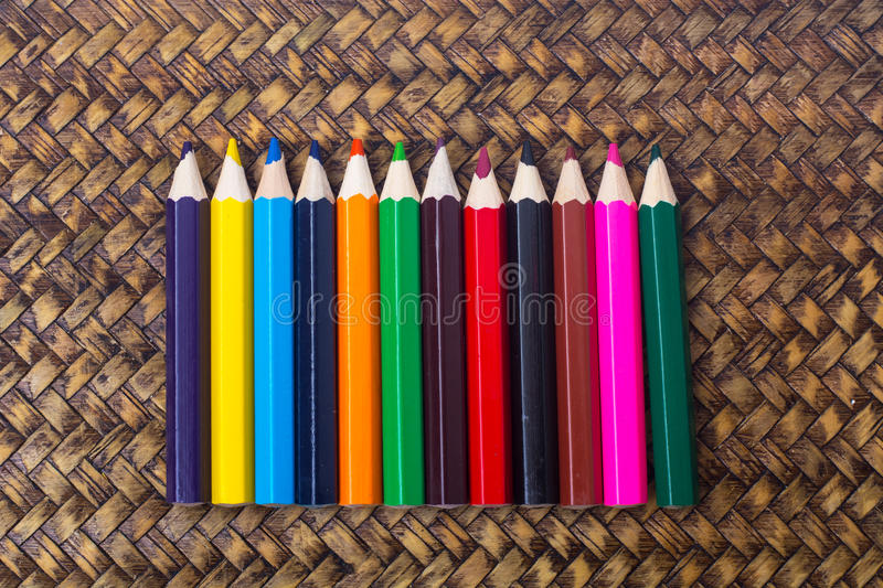 Colored school pencils on wooden wicker background stock photos
