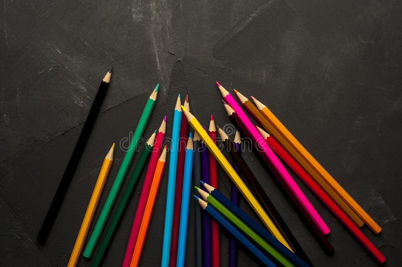 Colored sharpened pencils lie on the dark surface royalty free stock images