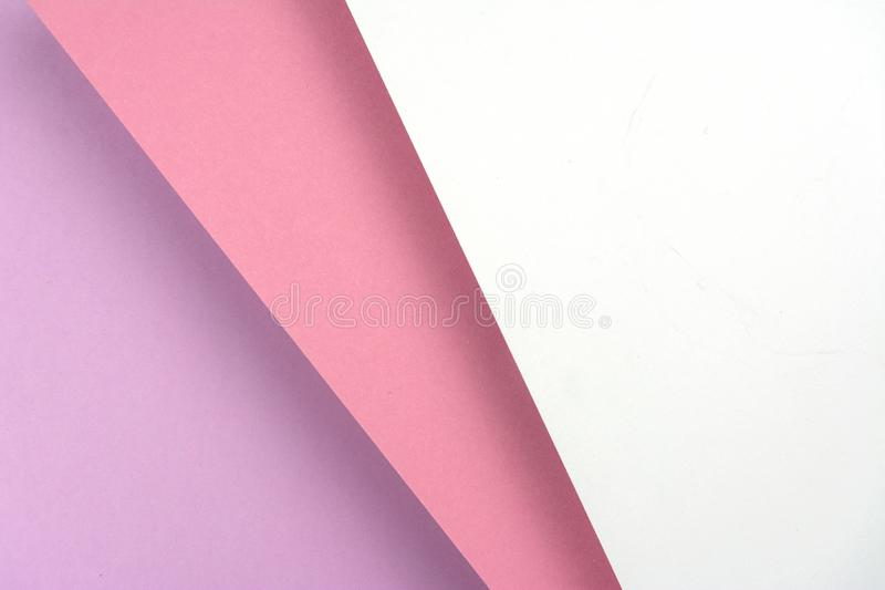 Colored sheets of paper lying on top of each other. The paper is pink, purple and white stock illustration