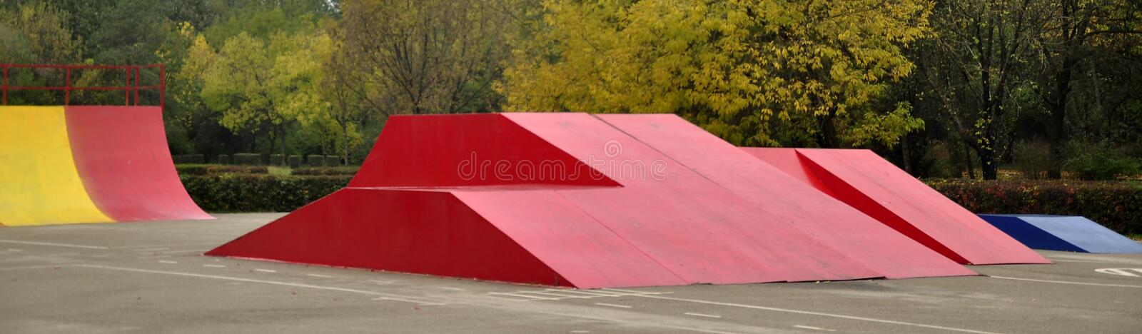 Colored skate ramps next to the woods. Autumn landscape on the background with place for playing the skateboard with colored ramps in the foreground stock images
