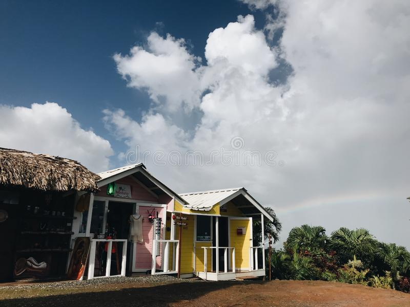 Colored souvenir shops on the mountain redonda. In Dominican Republic under cloudy sky with rainbow. Huge white clouds and harsh sunlight, red mud royalty free stock photos