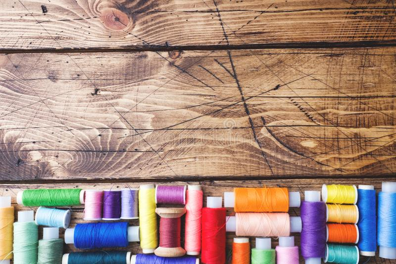 Colored spools of thread laid out in rows on wooden background. Copy space.  royalty free stock images