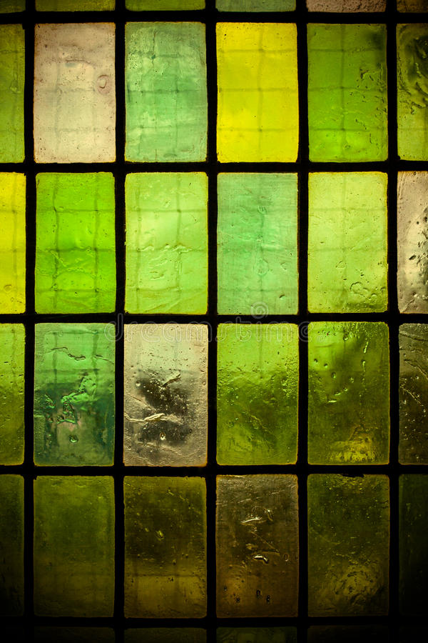 Colored stained glass window with regular block pattern green tone stock image