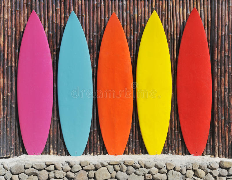 Colored surfboards. Leaning up against a wooden fence stock image