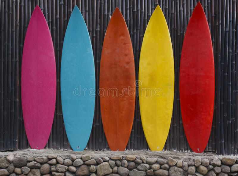 Colored surfboards leaning up against a wooden fence. On beach royalty free stock image