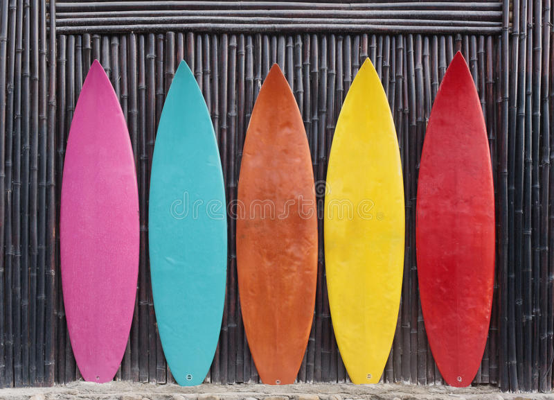 Colored surfboards leaning up against a wooden fence. On beach stock image