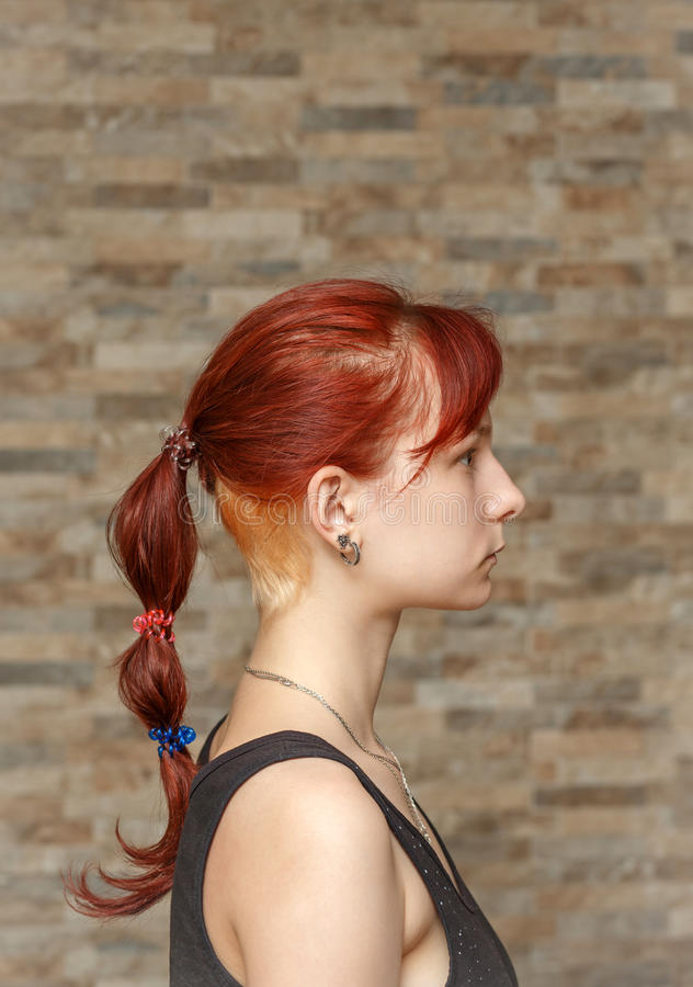 Colored tail and hidden undercut hair. Young model with colored tail and hidden undercut bleached hair stock image