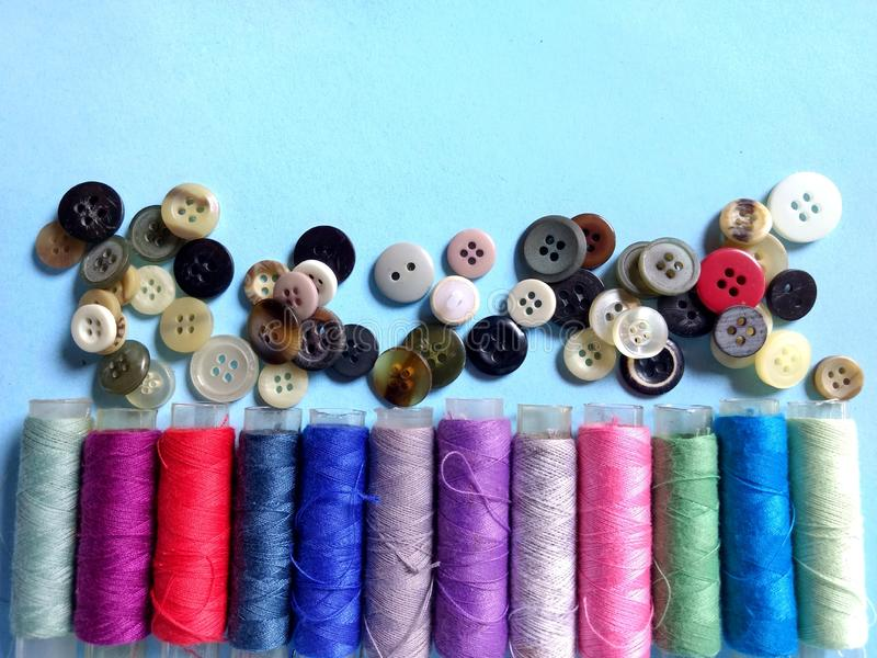 Colored thread cones with buttons on blue background stock photos